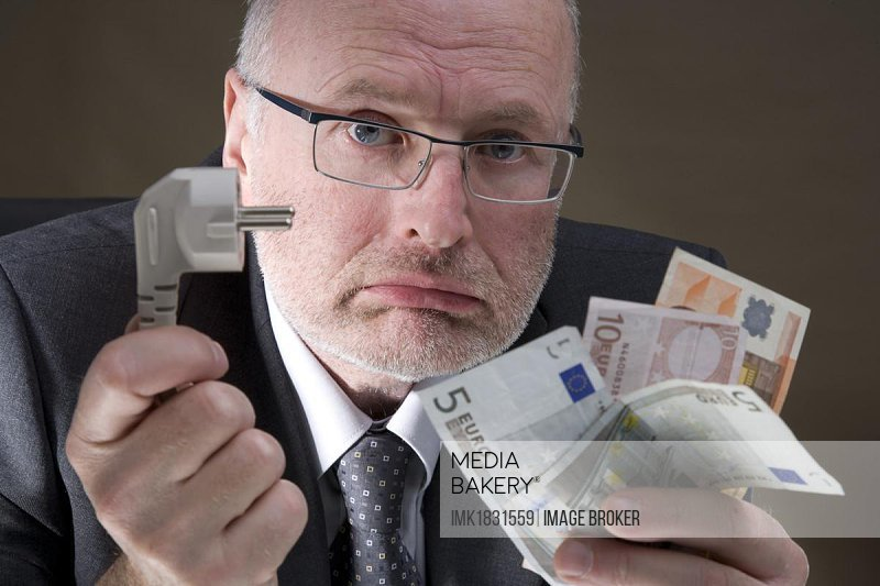 Man holding an electric plug and banknotes, expensive electricity