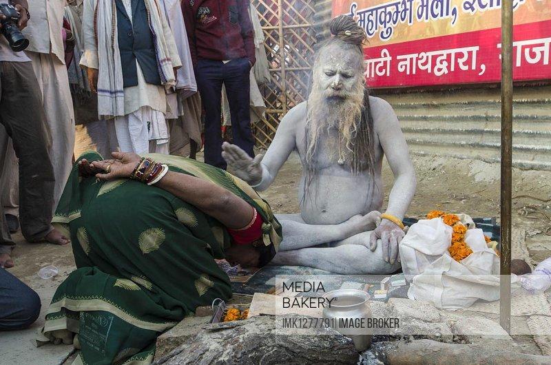 Shiva sadhu from Avahan Akhara, holy man, blessing a pilgrim at the Sangam, the confluence of the rivers Ganges, Yamuna and Saraswati, during Kumbha Mela festival, Allahabad, Uttar Pradesh, India, Asia