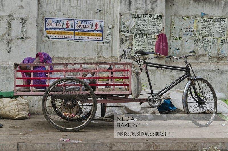 Rikshaw kuli sleeping in the back of his rickshaw, Kolkata, India, Asia