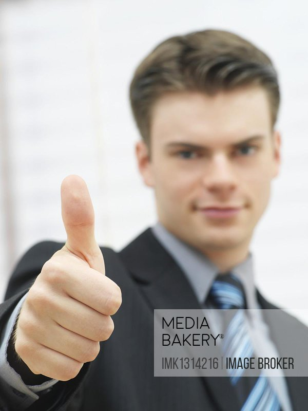 Businessman making a thumbs up gesture