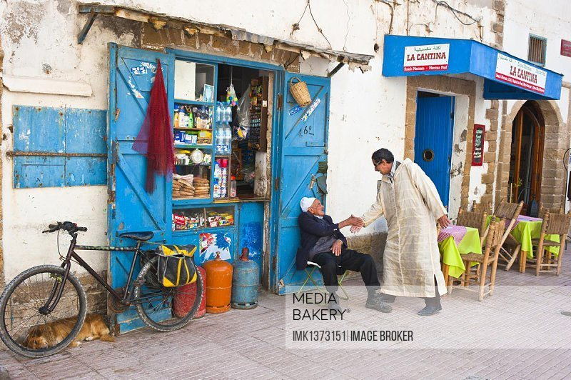Two men greeting each other in front of a small shop, Essaouira, Morocco, Africa