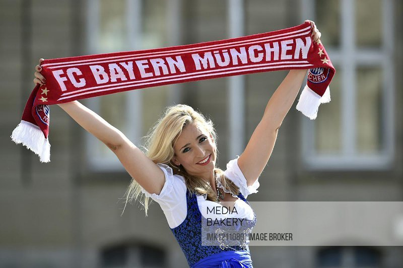Young woman wearing a dirndl, supporter of FC Bayern, holding up a fan scarf, Germany, Europe