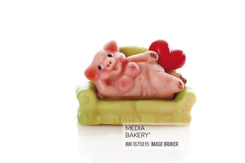 Frivolous marzipan pig with heart on a green sofa