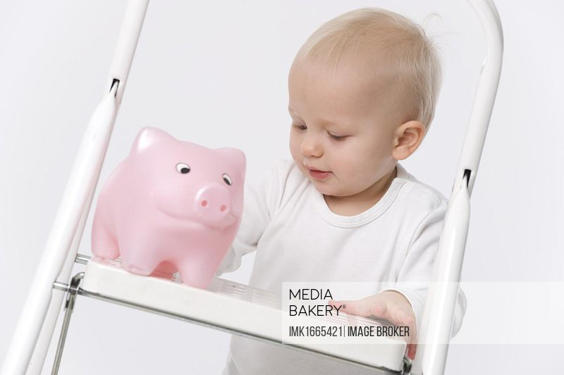 Toddler with piggy bank on a ladder