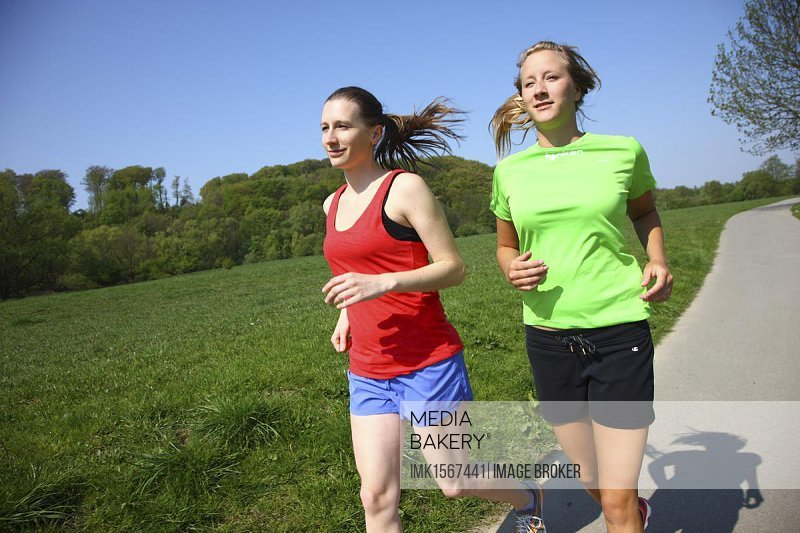 Two recreational runners, young women, 25-30 years, jogging