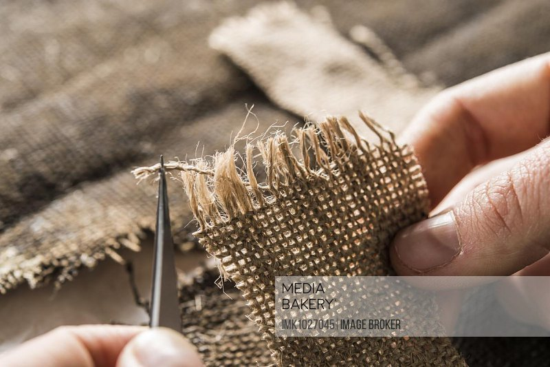 Restoration atelier,hand processing linen patch with thread bridges over crack in lent scarf, Munich, Bavaria, Germany, Europe