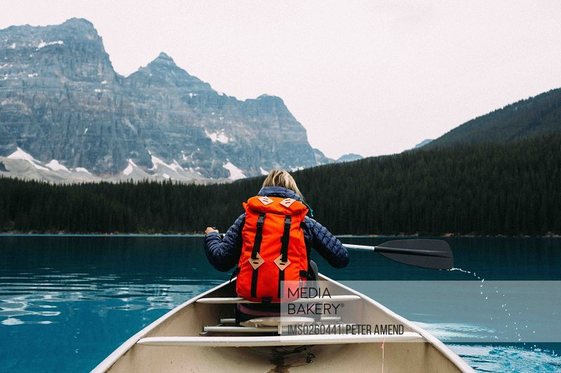 Rear view of mid adult woman paddling canoe Moraine lake Banff National Park Alberta Canada