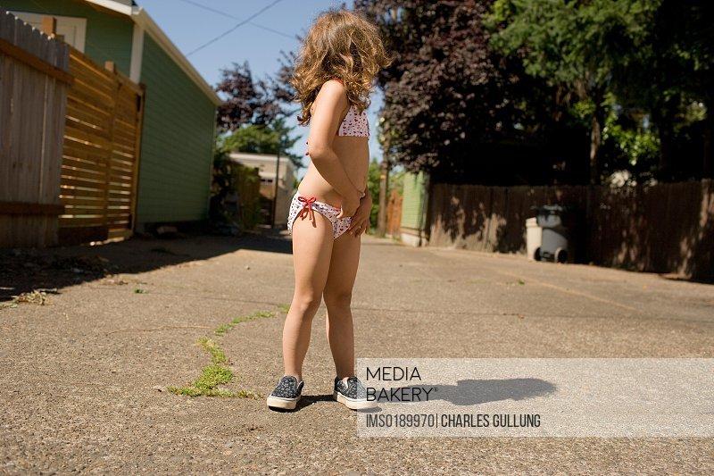 Girl wearing bikini on sidewalk