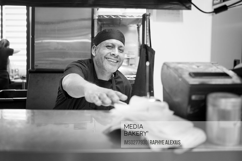 Chef in commercial kitchen smiling at camera