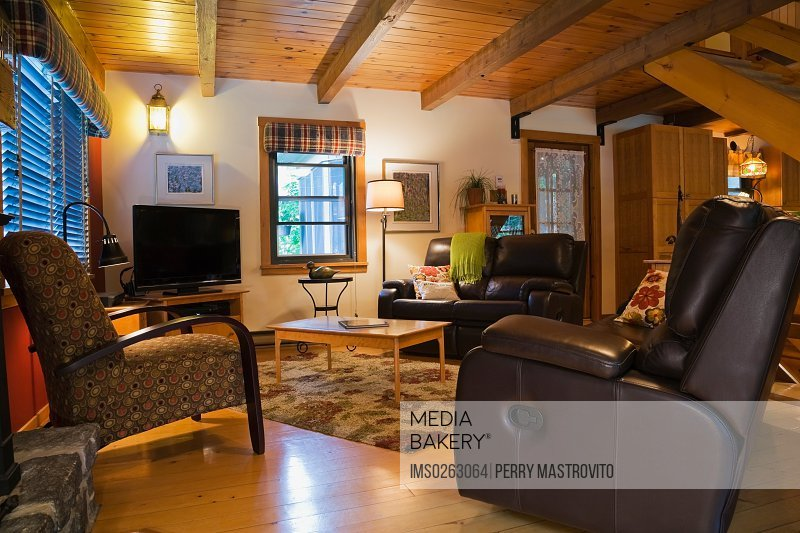 Photo by Image Source - Leather sofas and wooden coffee table in living  room of Canadian cottage style log home