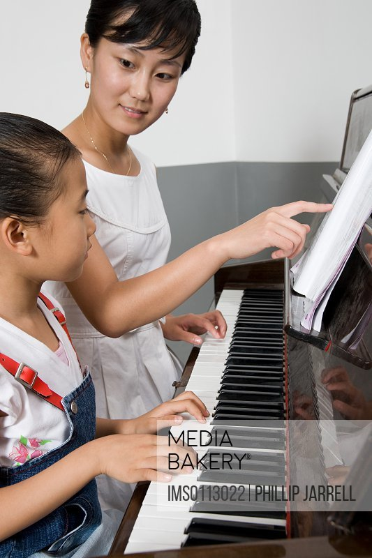A teacher helping a student play the piano