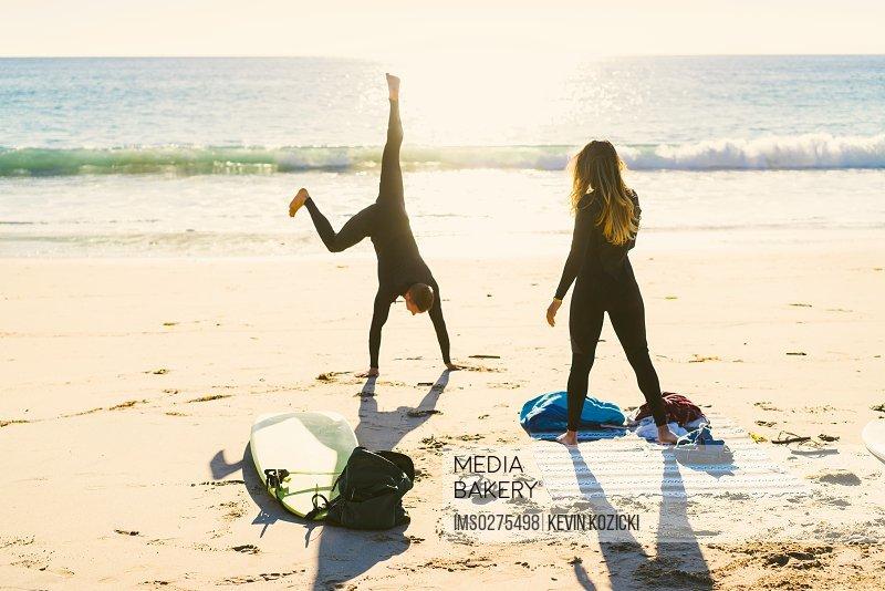 Surfing couple cartwheeling on Newport Beach California USA