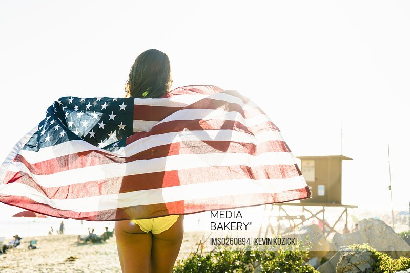 Rear view of young woman wrapped in American flag on Newport Beach California USA