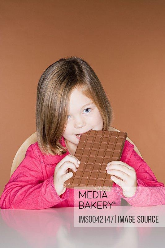 Girl biting a big bar of chocolate