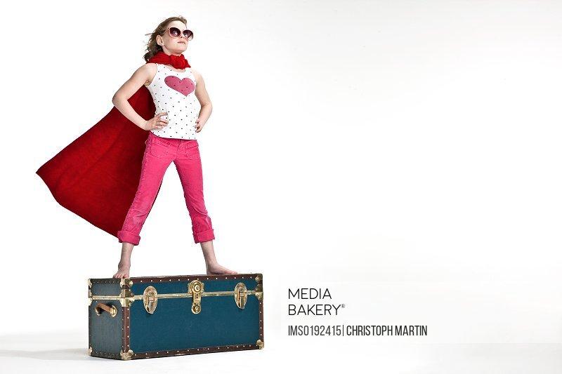 Girl standing on trunk suitcase dressed as superhero