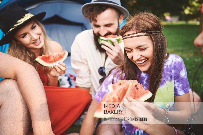 Young boho adult friends eating melon slices at festival