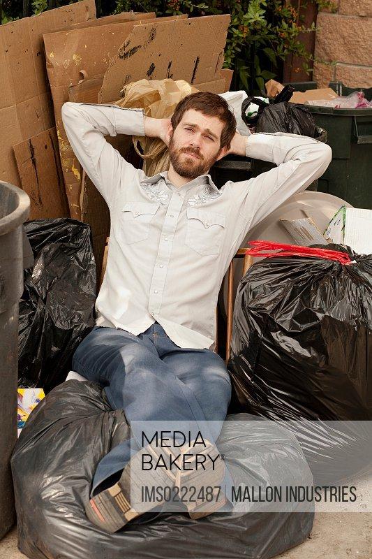 Man sitting on pile of bin bags