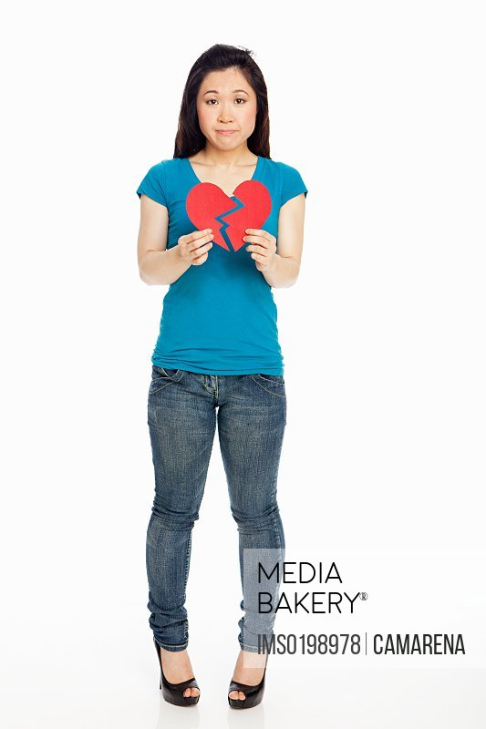 Young Japanese woman holding broken heart against white background