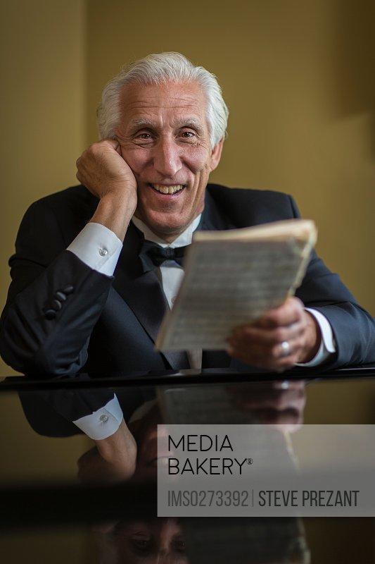 Portrait of senior man at piano holding sheet music