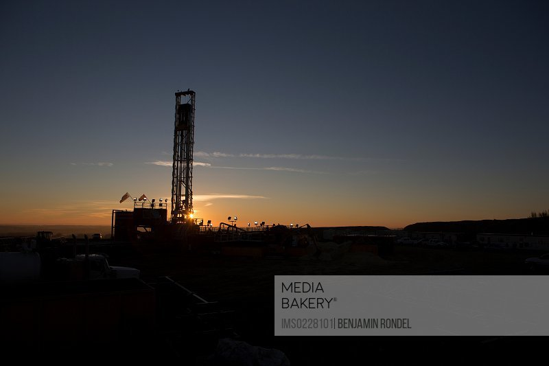 Silhouette of oil well in dry landscape
