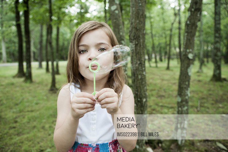 Girl blowing bubbles in forest