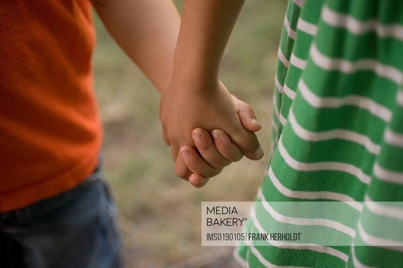 Girl and boy holding hands, close up