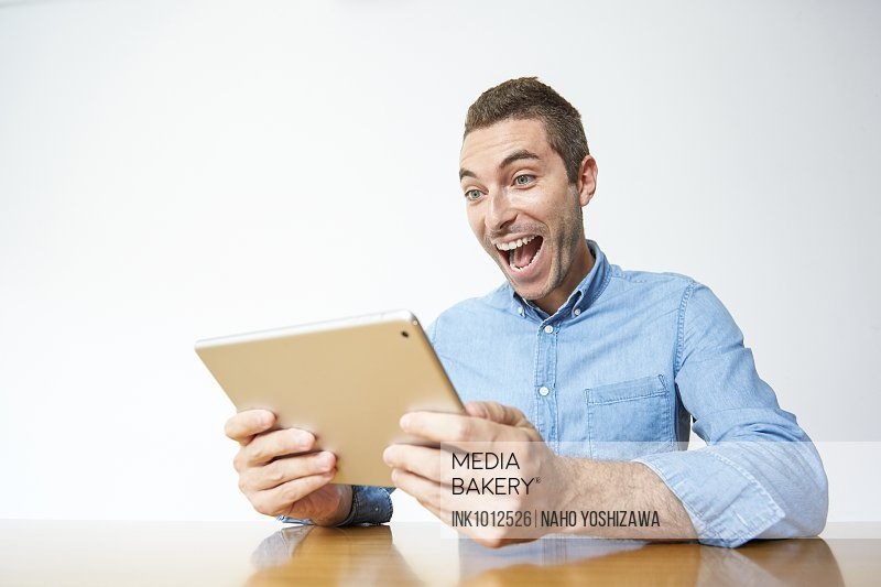 Caucasian man enjoying content on a tablet