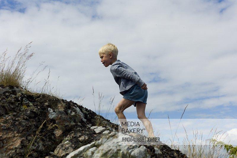 Boy climbing cliff
