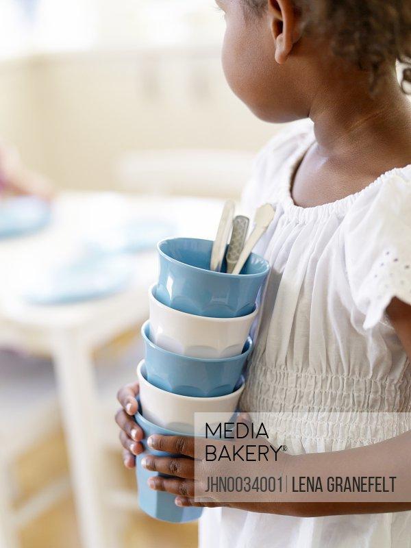 Girl carrying stack of mugs