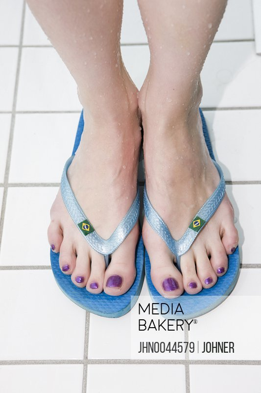 Photo by Johner Images - Woman wearing flip flops at swimming pool close-up