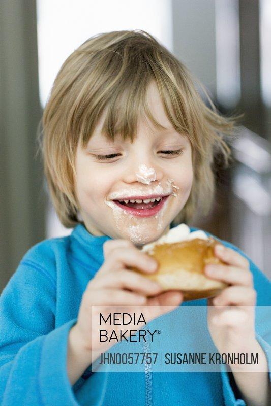 Smiling boy eating bun