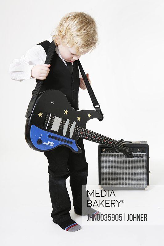 Studio shot of boy holding electric guitar
