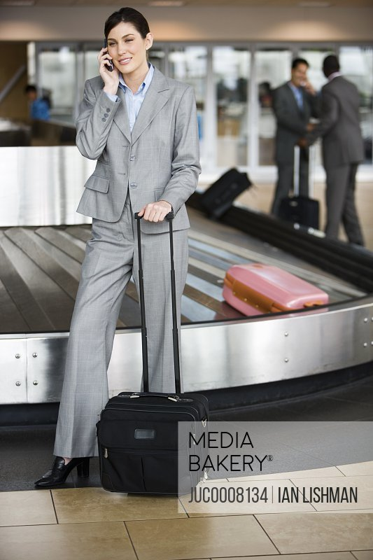 Businesswoman collecting luggage from baggage carousel in airport, using mobile phone, smiling
