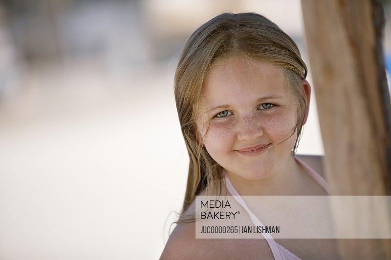 Girl (6-8) standing beneath sunshade on beach, smiling, portrait