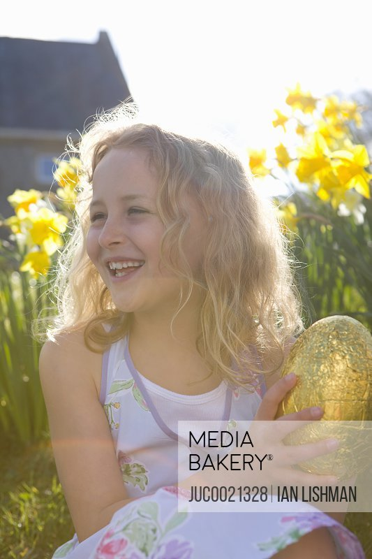 Girl finding chocolate Easter egg in flowers