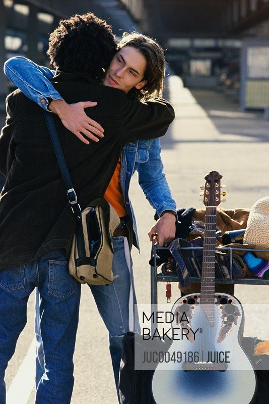 Young guitarist embracing friend