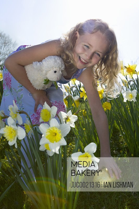 Girl finding chocolate Easter eggs in flowers