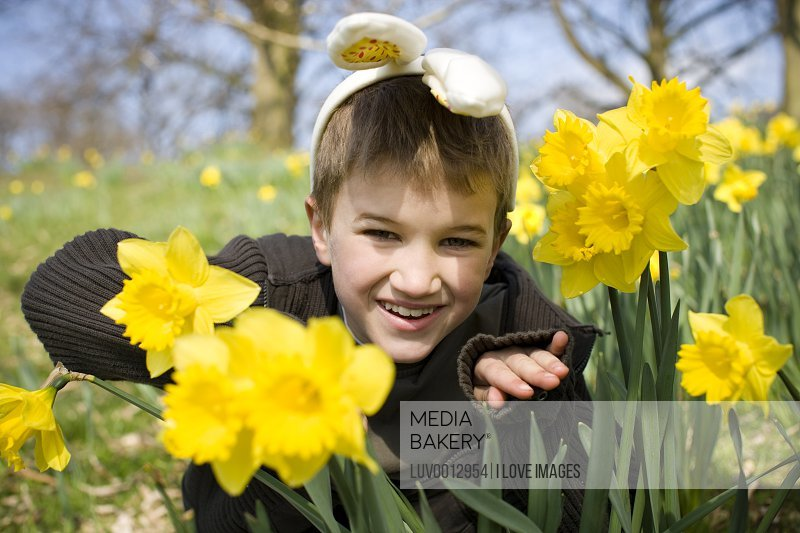 A young boy peering through daffodils wearing bunny ears
