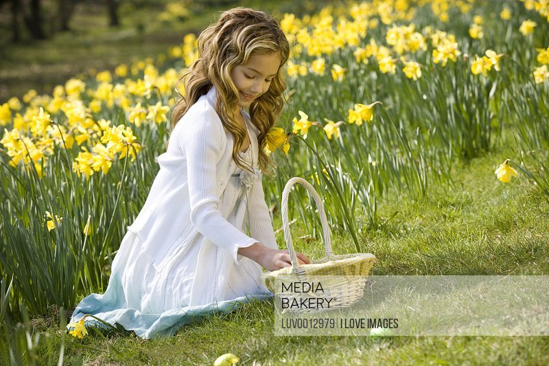 A young girl collecting Easter eggs