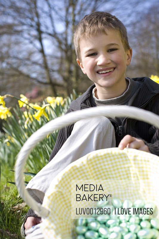 A young boy holding a basket full of Easter eggs