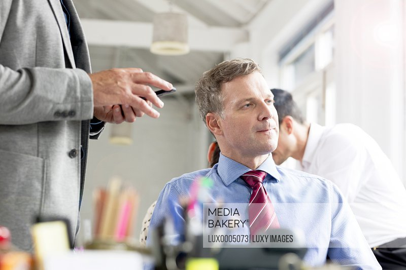 Mature businessman thinking at desk in office