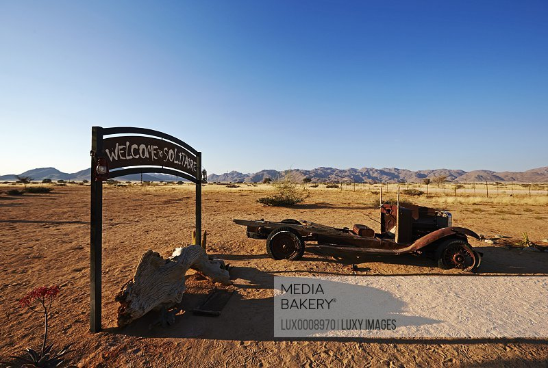 Welcome sign by abandoned truck in desert