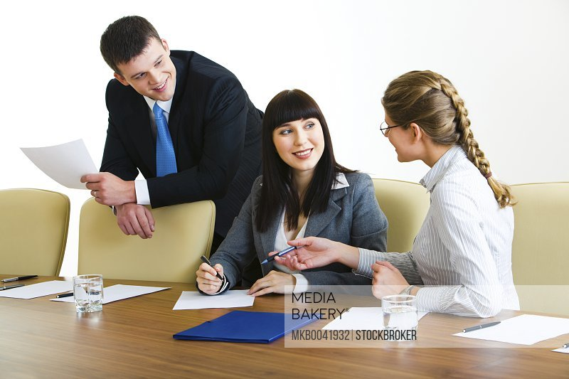 Photo of three professionals discussing conditions of transaction