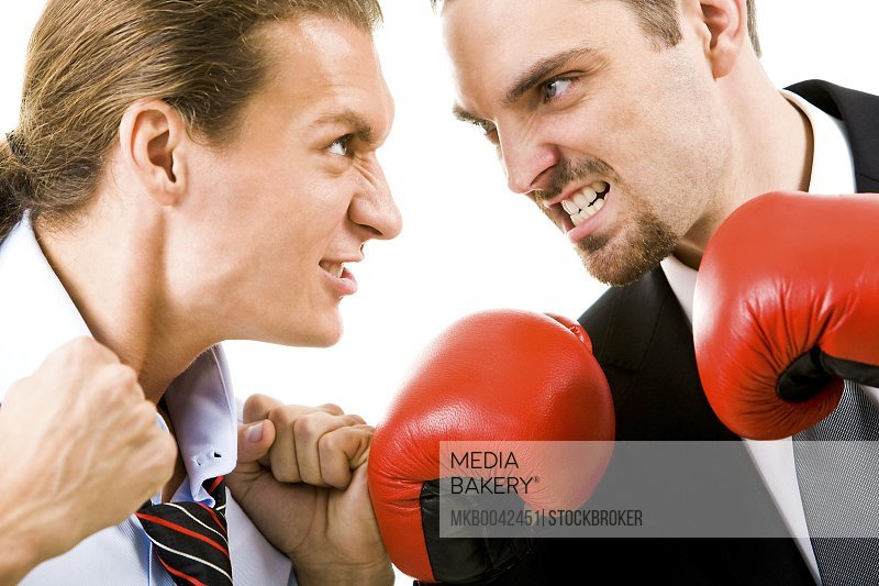 Portrait of aggressive businessmen in boxing gloves looking at each other with angry grin
