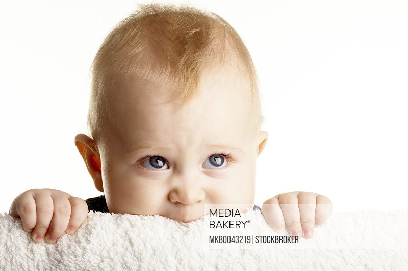 Face of curious baby peeping out of board in isolation