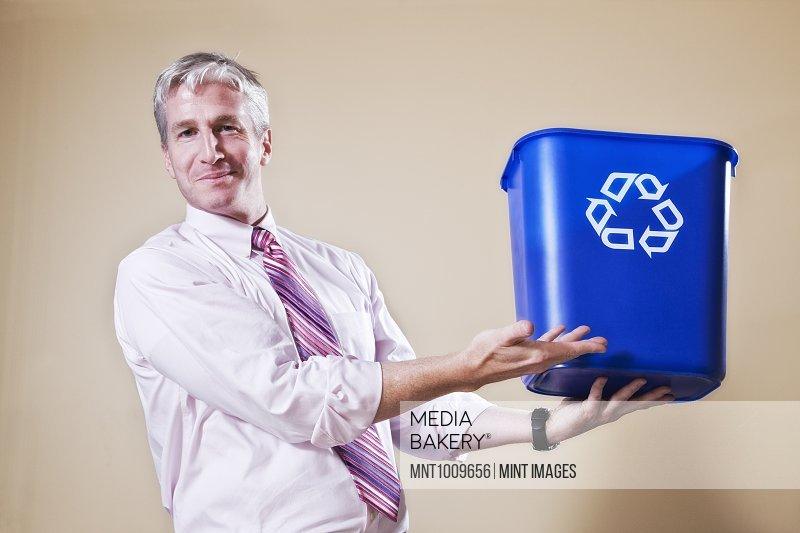 Caucasian man in shirt and tie holding a recycle waste bin.