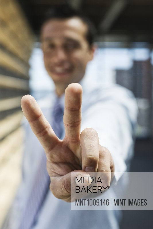 Businessman gesturing a victory sign to the camera.