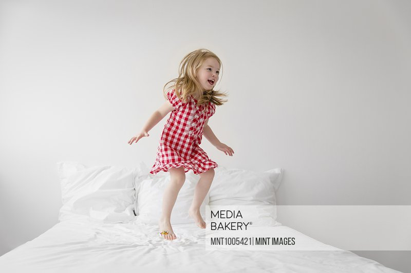 9fd38fc90e7 Smiling blond girl wearing red and white checkered dress jumping on bed  with white duvet.