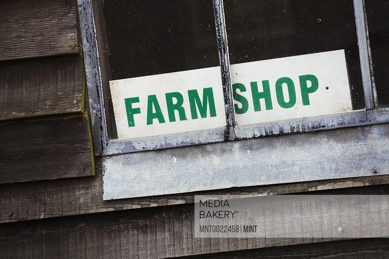 A sign for a farm shop visible through a window