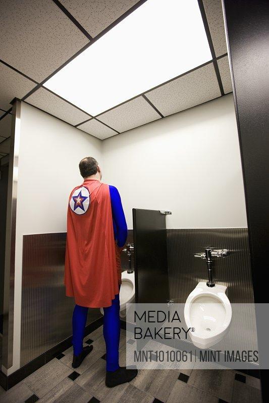 An office super hero takes a bathroom break between super hero feats.
